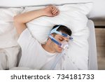 Small photo of High Angle View Of Man Lying On Bed With Sleeping Apnea And CPAP Machine