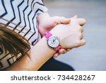 girl looks time on her pink... | Shutterstock . vector #734428267