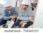 two builders with clipboard... | Shutterstock . vector #734565727