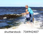 Man Helps A Boy With Fishing...