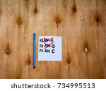 Small photo of A note with plan a ,plan b ,plan c text and a pen on rustic wooden table