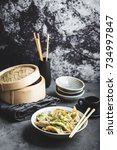 Small photo of Asian dumplings in bowl, chopsticks, bamboo steamer, plates. Asian table setting. Chinese dumplings for dinner. Selective focus. Asian style decoration. Chinese fresh homemade food. Closeup