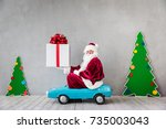 santa claus riding car.... | Shutterstock . vector #735003043