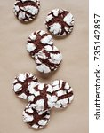 Small photo of Chocolate crinkle cookies on the table covered with craft paper