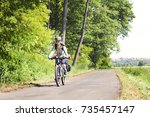 woman bicyclists riding on... | Shutterstock . vector #735457147