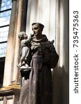 Small photo of Wooden statue of St Anthony (St Antonius) holding a child in his arms. Statue of Saint Anthony in a church, natural light coming down from above.