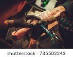 tattoo artist makes a tattoo on ...   Shutterstock . vector #735502243