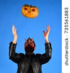 Small photo of Man wearing scary makeup throws pumpkin up on blue background. Devil or monster with October decorations. Demon with horns and concentrated face holds carved jack o lantern. Halloween party concept