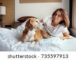 woman and beagle dog wake up... | Shutterstock . vector #735597913