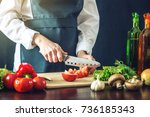 the chef in black apron cuts... | Shutterstock . vector #736185343