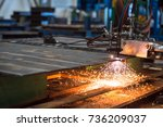 Small photo of Acetylene torch semi auto machine cutting metalwork fabrication with bright sparks in factory.