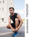 young man in sportswear tying...   Shutterstock . vector #736233187