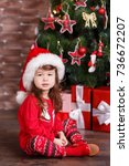 Small photo of Young brunette dolly lady girl stylish dressed in red pullover sweater warm sox Santa hat shoes smiling posing sitting in studio winter christmas tree with presents with pout lips and pink cheeks