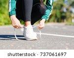 girl ties up sneakers   Shutterstock . vector #737061697