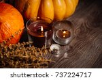 Small photo of composition for decorating the house for halloween, lie yellow and orange pumpkins on each other, burning scented candles, lies a branch of dry grass