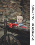 Small photo of Baby newborn girl with blue eyes wearing tartan check dress shirt and pink shawl bandana posing on wooden old style retro wagon cart trundle with apples and red comforter plaid wrap.