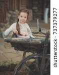 Small photo of Baby young girl with blue eyes with brunette plait hair wearing white dress shirt and posing on wooden old style retro wagon cart trundle posing looking to camera.