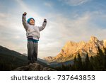 Small photo of a child conquers the summit, loose his proud arms, in the background the Alps