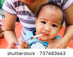 Small photo of Mother is administering fever medication to infants.