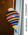 Small photo of front view look of a children adult vintage old antic toy handmade colorful hanging from a rope with a window on the background