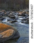 Small photo of Soana Valley, Piedmont, Italy - October 2013: Mountain stream with boulders covered by red lichens.