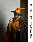 Small photo of Halloween wizard reading book on brick wall. Man in witch hat and cloak with raised finger. Magic and evil spell. Mystic story, manuscript and fairytale. Philosophy, wisdom and knowledge concept.