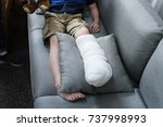 kid with injured leg is sitting ... | Shutterstock . vector #737998993