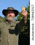 Small photo of A prospector holds up a specimen of an alluvial gold nugget. Focus on the nugget.