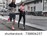 Small photo of Never stop. Full length of young couple in sport clothing running through the city street together