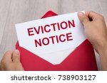 Small photo of Close-up Of A Person's Hand Holding Eviction Notice In Red Envelope