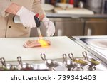 Stock photo chef hands with torch burner torch blowing fire on meat chef is preparing duck breast 739341403