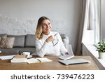 Small photo of Indoor portrait of cheerful middle aged female chief editor with thick loose hair sitting at her workplace and laughing while reading satirical verses, holding book, enjoying author's writing style