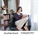 Small photo of Close up beautiful young asian woman short hair read a book in living room at home