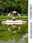 Small photo of Aeration waterwheel and reflective image in calm water