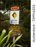 Small photo of Kauai, Hawaii - 3/27/2009: A sign warning of high surf and treacherous trails, located in a trailhead parking lot on the north shore of the island of Kauai, Hawaii.