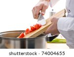 Male chef adding cut tomatoes to pot on stove - stock photo