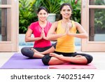 two young women sitting on mats ... | Shutterstock . vector #740251447