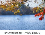 Small photo of Autumn on Muskoka Lakes, Ontario, Canada. Canoeist Paddling a Canoe on Muskoka Lake