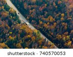Small photo of Scenic aerial view of a car driving on a winding road through the colorful fall colors in the Quebec Laurentian forest.