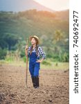 Small photo of Farmer woman, Farmer standing holding a hoe