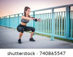 Small photo of Young athletic woman doing squat exercises on sidewalk over the bridge outdoors.