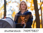 a young mother with a stroller... | Shutterstock . vector #740975827