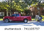 Small photo of Red work pick up truck pulling small cement mixer parked on street in traditional neighborhood