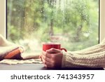 red mug of hot drink in hand ... | Shutterstock . vector #741343957