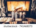 feet in woollen socks by the... | Shutterstock . vector #741468373