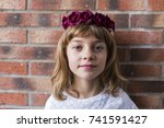 Stock photo portrait of a beautiful little girl wearing a red crown roses on her head brick background 741591427