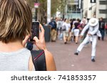 Small photo of San Francisco, USA - September 13th, 2017: A woman is recording a video with her mobile phone of a street performer costumed like Michael Jackson, San Francisco.