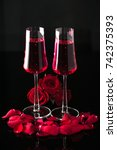 Stock photo a pair of champagne glasses with pink champagne a bunch of ruby red roses and rose petals 742375393