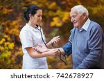 nurse measuring old patient's... | Shutterstock . vector #742678927