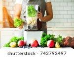 woman blending lettuce leaves ... | Shutterstock . vector #742793497
